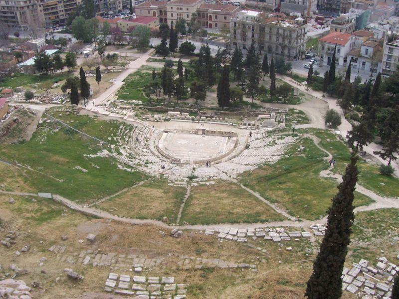 Teatro de Dioniso, visto do alto da Acrópole, com parte da moderna Atenas ao fundo